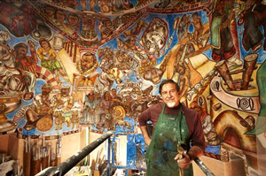 Santa Fe artist Frederico Vigil in front of his latest fresco.