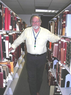 Archdiocese of Boston Archivist Robert Johnson-Lally among records at the Pastoral Center in Braintree.   Photo Credit: Nancy Maloof