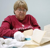 Janice Gilbert, a volunteer with the DeKalb Genealogical Society, packs up old records Tuesday to be moved to the former Veterans Affairs building in Fort Payne. Photo by Melissa Smith.
