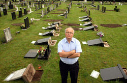 Councillor Philip Owen by the overturned headstones