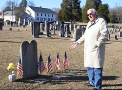 Cary Grant stands near the grave of one of the 52 Revolutionary War soldiers buried in the cemetery at Bethel Presbyterian Church. The church is in the background. Photo by Jennifer Becknell.